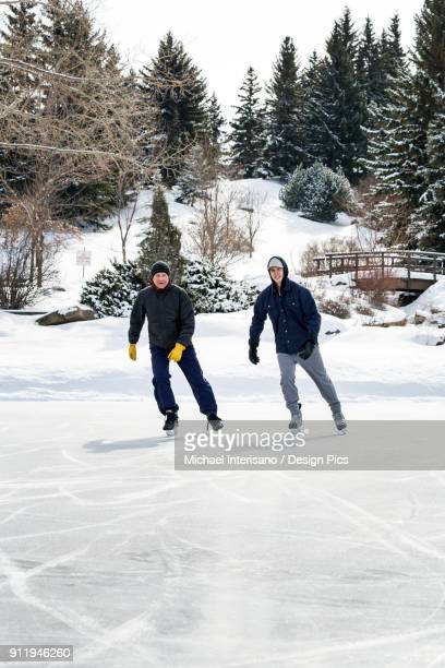 Father And Son Skating On Pond With Snow Covered Bridge In The Background