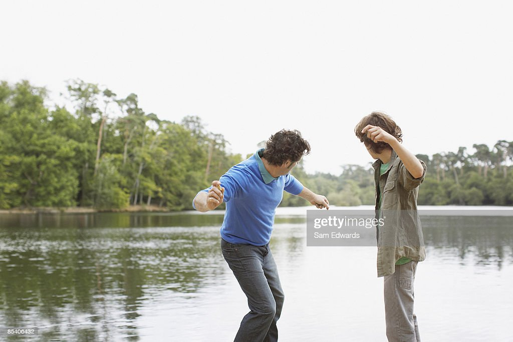 Father and son skimming stones in lake : Stock Photo