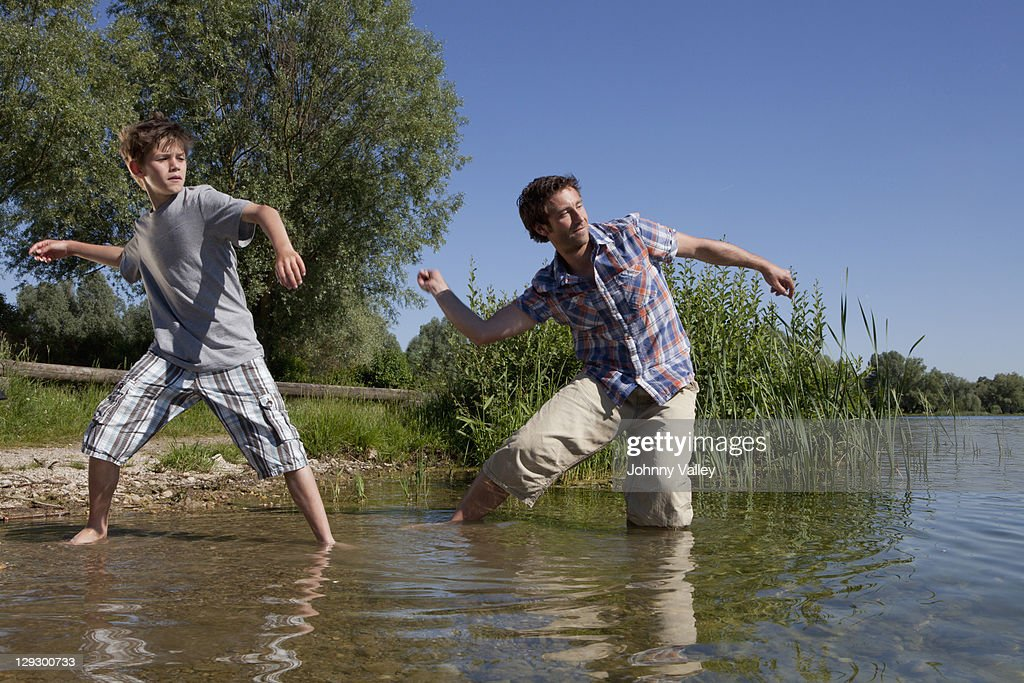 Father and son skipping rocks on lake  : Stock Photo