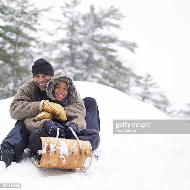 father and son sledding - tobogganing stock pictures, royalty-free photos & images