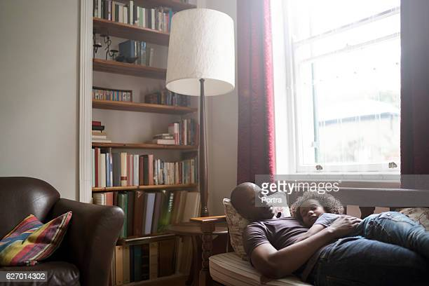Father and son sleeping by window at home