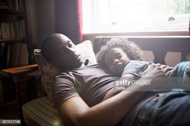 Father and son sleeping in brightly lit home