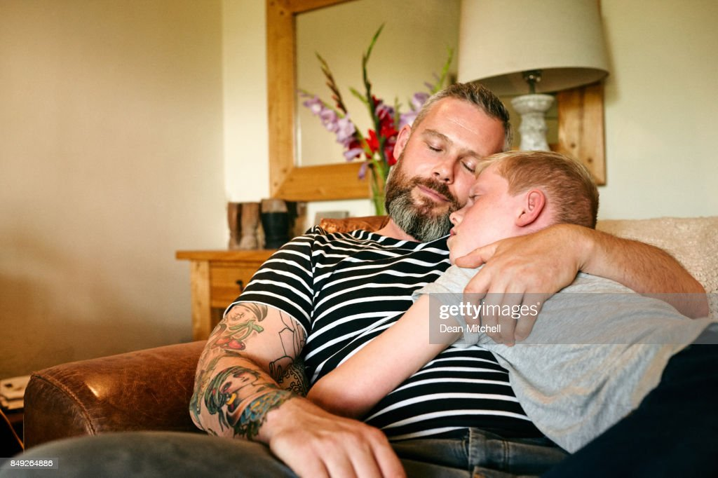 Father and son sleeping on sofa : Stock Photo