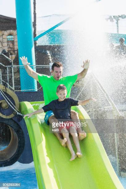 Father and son sliding down slide at water park