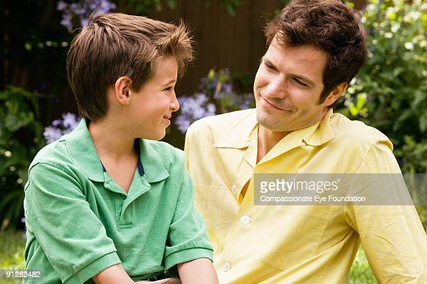 "father and son smiling at one another - ""compassionate eye"" stock pictures, royalty-free photos & images"