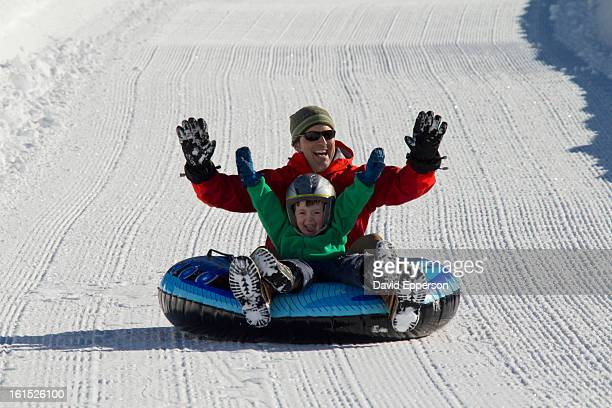 Father and son snow sledding/tubing