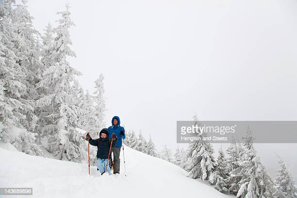 father and son snowshoeing on hillside - family with one child stock pictures, royalty-free photos & images