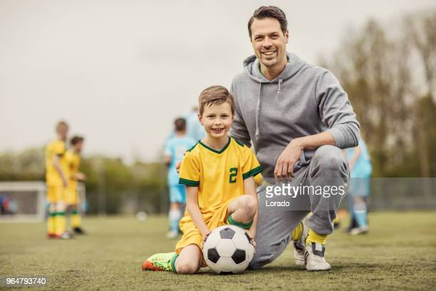 pai e filho de jogadores de futebol a posar para a foto durante uma sessão de treinamento de futebol - uniforme de equipe - fotografias e filmes do acervo