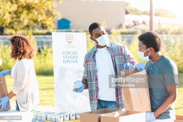 father and son spend time together at food drive - giving tuesday stock pictures, royalty-free photos & images