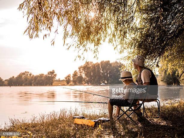 Vater und Sohn verbringen Sie Ihren Tag im Süßwasser angeln.