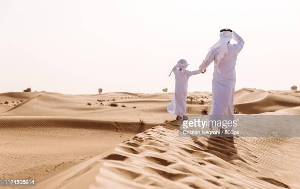 father and son spending time in the desert - qatar fotografías e imágenes de stock