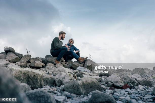 father and son spending time together outdoors, taking a break, sitting on stones - kontinuität stock-fotos und bilder