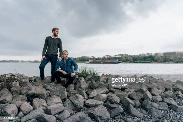 father and son spending time together outdoors, taking a break, sitting on stones - successor stock pictures, royalty-free photos & images