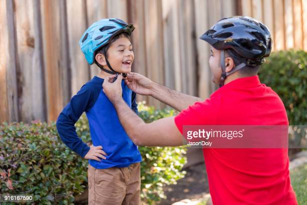 father and son sports safety - cycling helmet stock pictures, royalty-free photos & images