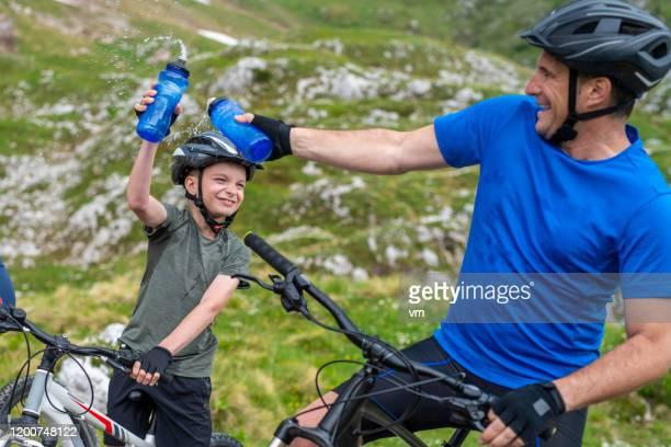 far och son sprutar vatten under en cykling vatten paus - slovenien bildbanksfoton och bilder
