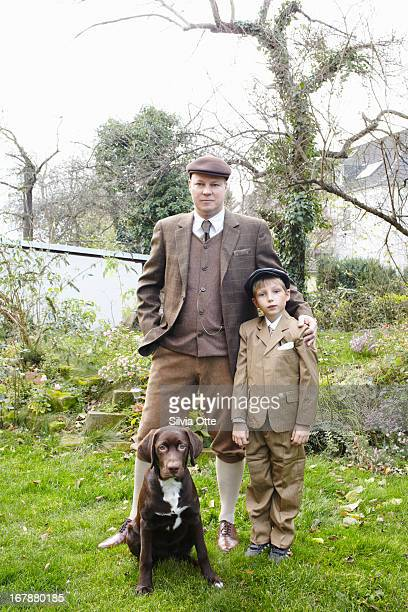 Father and son standin with their dog in garden