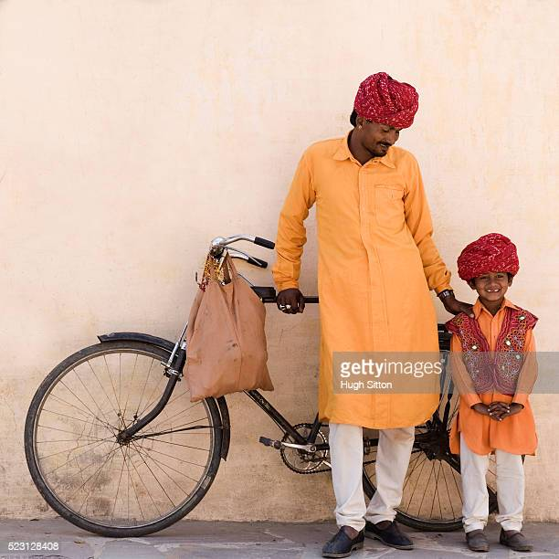 father and son standing by bicycle - hugh sitton india stock pictures, royalty-free photos & images