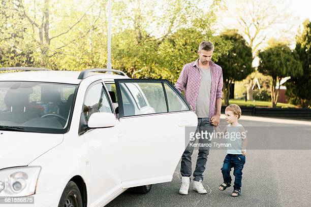Father and son standing by car on street