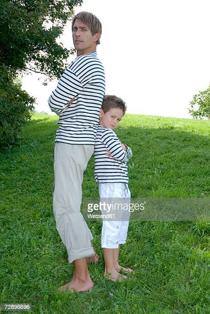 Father and son (4-7) standing in park, back to back