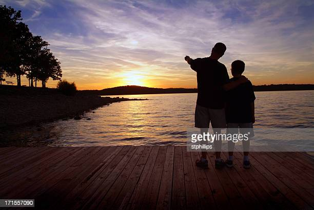 Father and Son Standing on a Boat Dock at Sunset