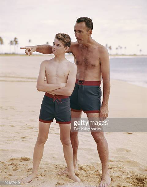 father and son standing on beach, father pointing  - archival stock pictures, royalty-free photos & images