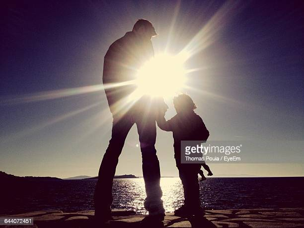 father and son standing on shore during sunny day - ver a hora stockfoto's en -beelden
