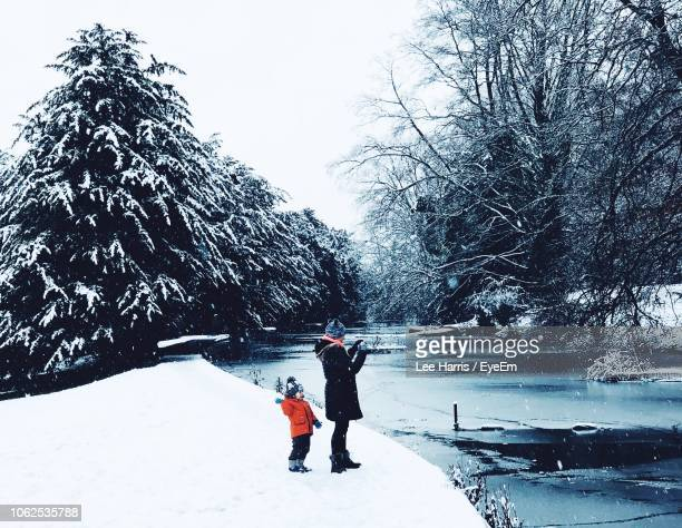 Father And Son Standing On Snow By Lake