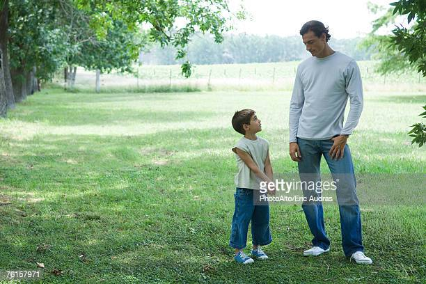 'Father and son standing outside on grass, looking at each other'