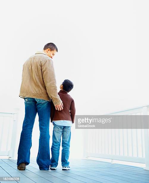 Father and son standing together while at a porch