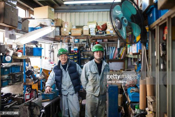 father and son steel workers together in the shipbuilding industry - ジャンプスーツ ストックフォトと画像