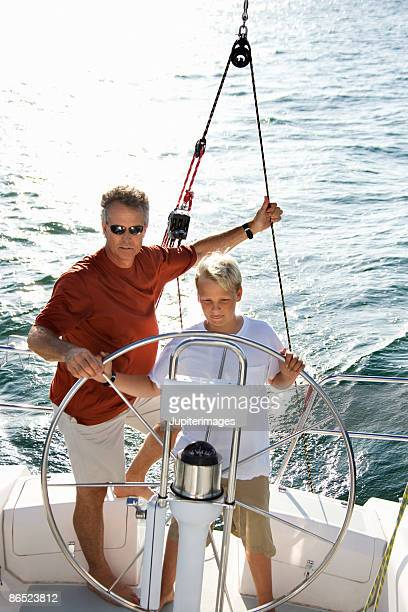 Father and son steering boat