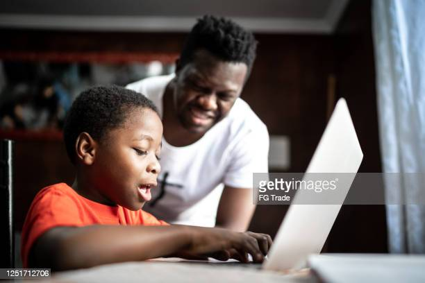 father and son studying with laptop on a online class at home - remote location stock pictures, royalty-free photos & images