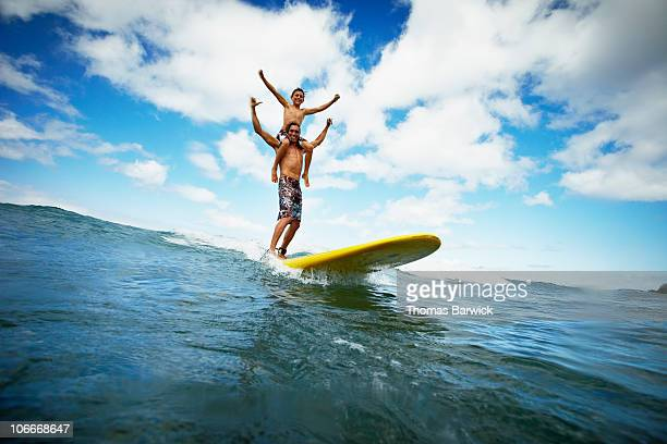 Father and son surfing boy on shoulders
