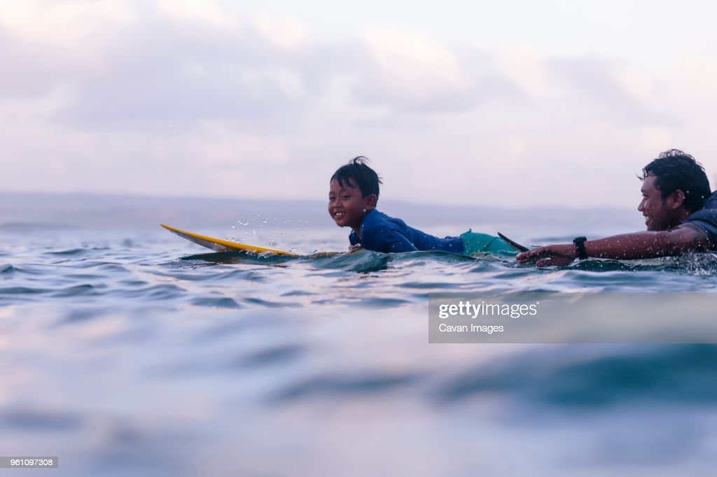 Father and son surfing in sea against sky : Stock Photo