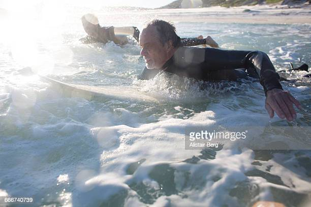 father and son surfing together - paddling stock pictures, royalty-free photos & images
