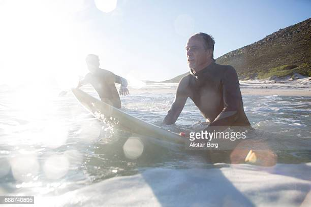 father and son surfing together - brightly lit stock pictures, royalty-free photos & images