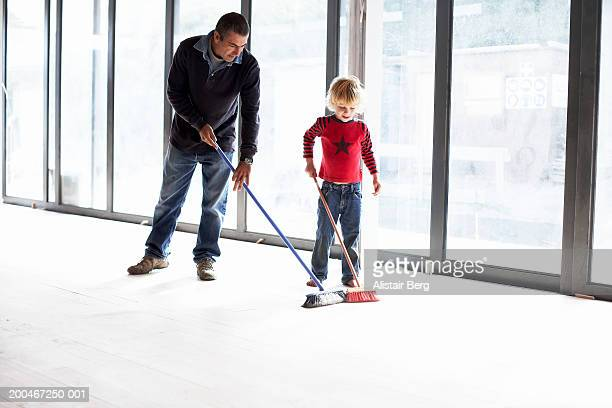 Father and son (4-6) sweeping floor in empty room