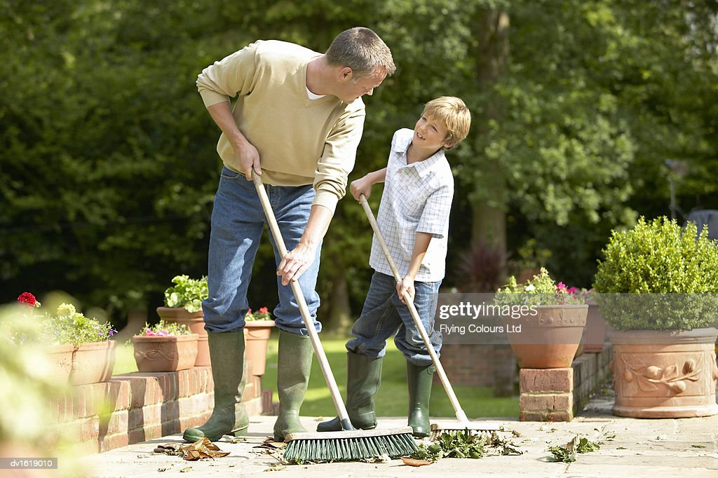 A Father and Son Sweeping Leaves in a Garden : Stock Photo