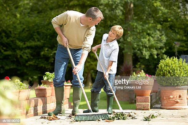 A Father and Son Sweeping Leaves in a Garden