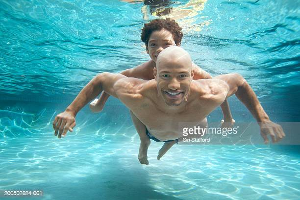 Father and son (7-9) swimming underwater