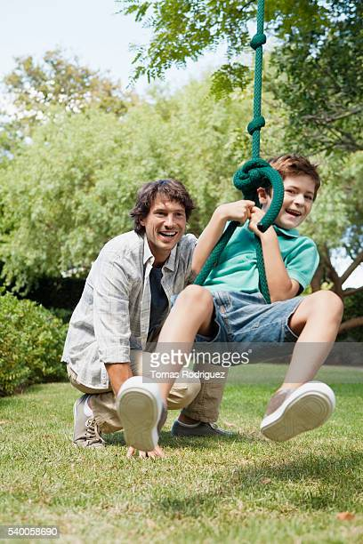 father and son (6-7 years) swinging in garden - 6 7 years stock pictures, royalty-free photos & images