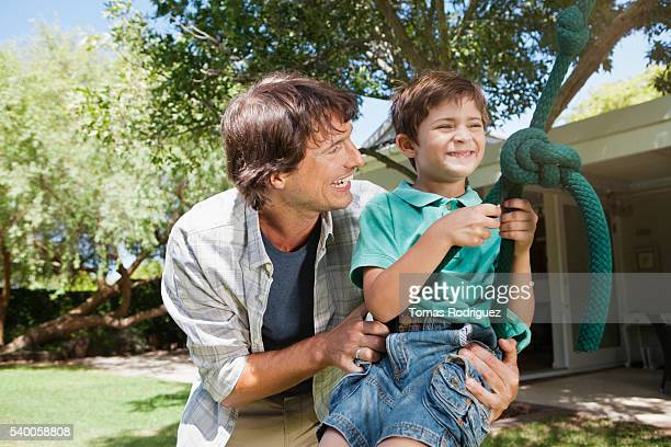 father and son (6-7 years) swinging in garden - 25 29 years stock pictures, royalty-free photos & images