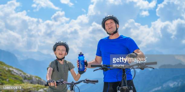 father and son taking a break during mountain biking - fingerless gloves stock pictures, royalty-free photos & images