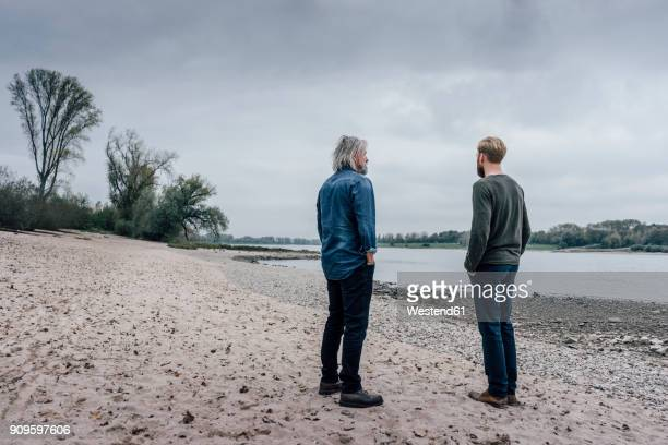 father and son taking a stroll at rhine river, meeting to talk - stehen stock-fotos und bilder