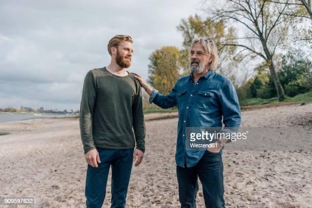 father and son taking a stroll at rhine river, meeting to talk - hand auf der schulter stock-fotos und bilder
