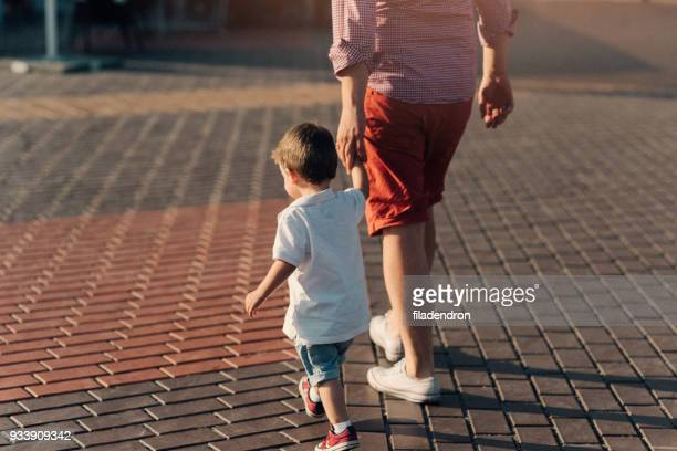father and son taking a walk - pavement stock pictures, royalty-free photos & images