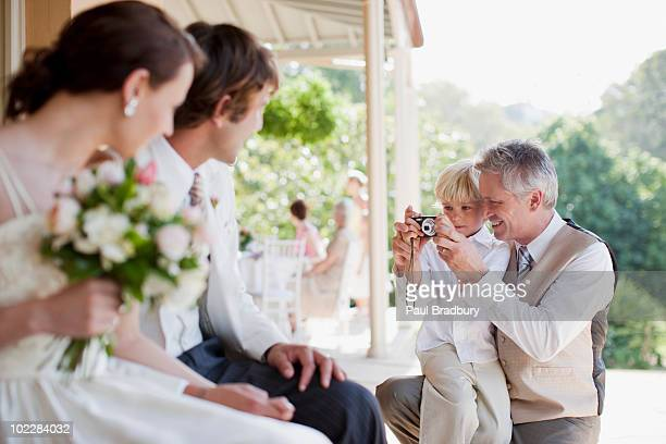 Father and son taking picture of bride and groom