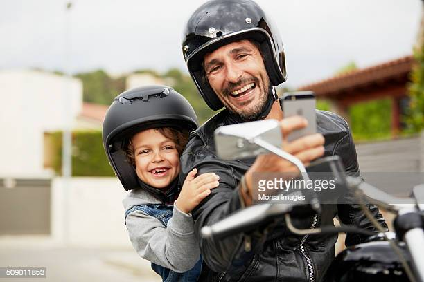 father and son taking self portrait on motorbike - sportschutzhelm stock-fotos und bilder