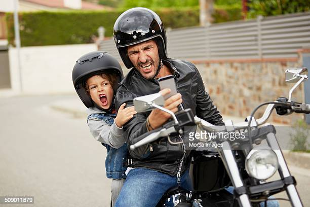 Father and son taking self portrait on motorbike