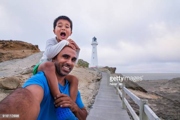 father and son taking selfie with castlepoint lighthouse in background. - wellington new zealand stock photos and pictures